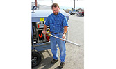 A user displaying the HandiFueler Ground Support Fuel Service Cart (AGE Refueler)'s ridgid defuel wand,