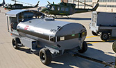 A HandiFueler Ground Support Fuel Service Cart (AGE Refueler) being towed on a Air Force flightline.